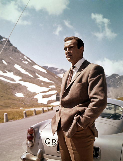 Sean Connery posing next to Aston Martin whilst filming Goldfinger – Surplus Store