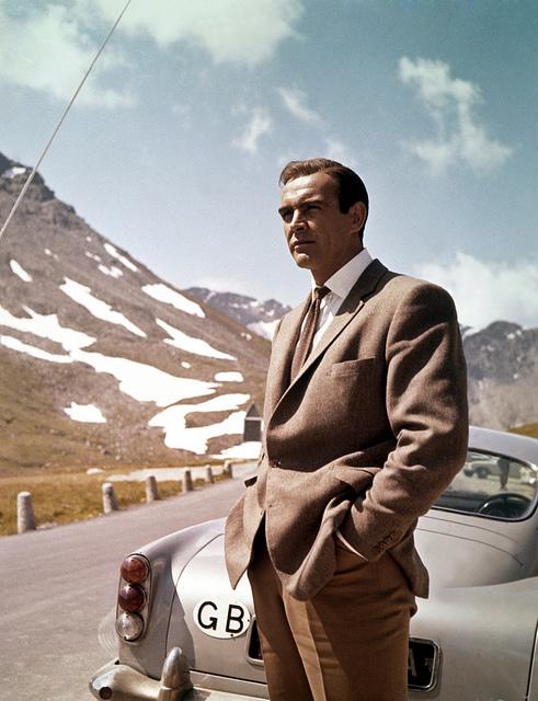 Sean Connery posing next to Aston Martin whilst filming Goldfinger – Surplus Store