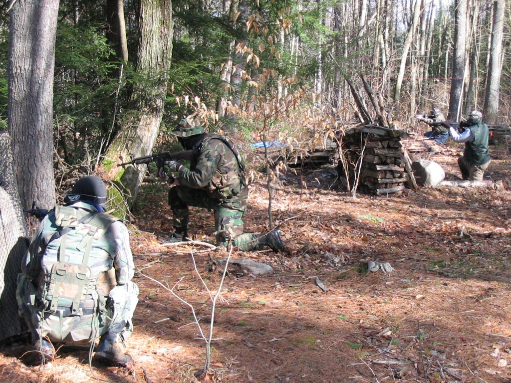 Team playing airsoft in a forest using Surplus Store BB guns for sale