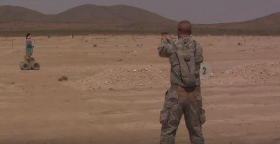Marine aiming at robot target during training