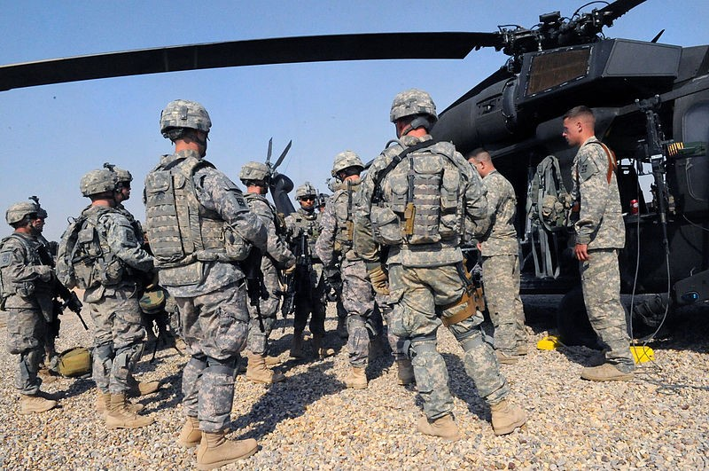 U.S. Army soldiers standing next to a helicopter