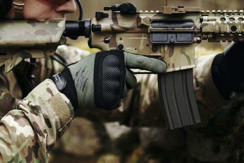 A man wearing gloves, aiming his airsoft gun