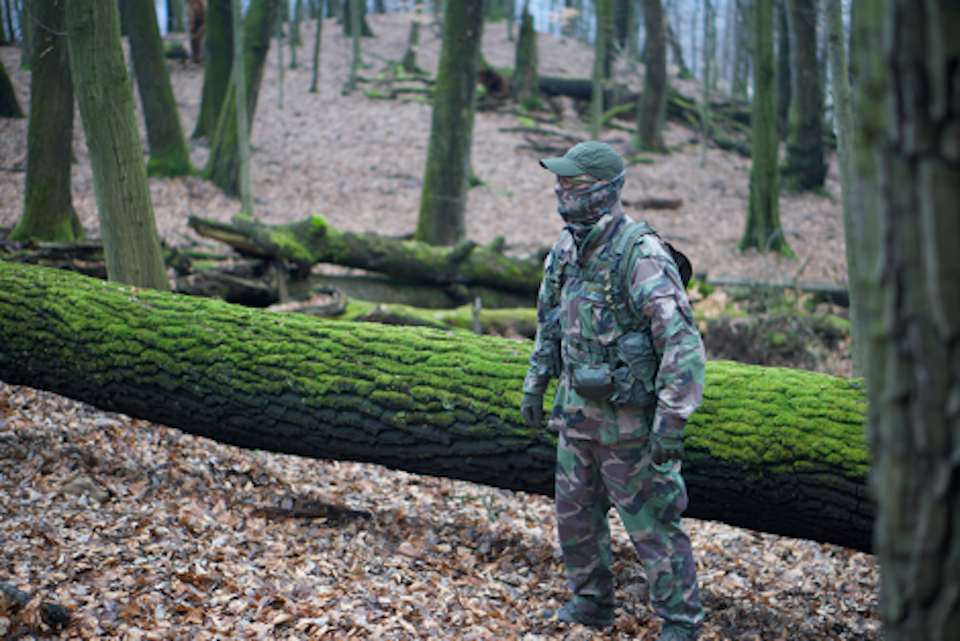 A man in camouflage gear in the woods