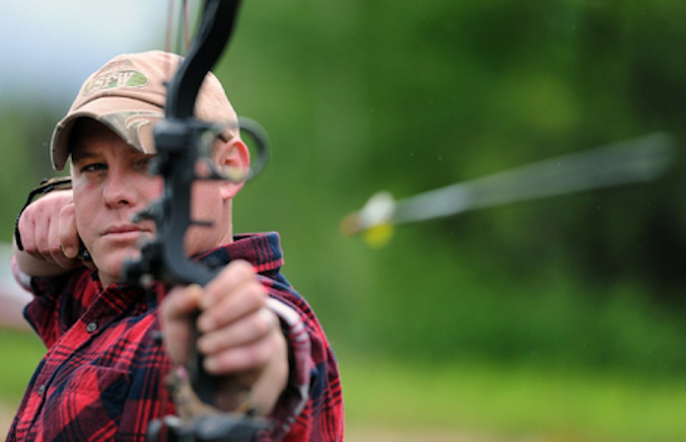 A man aiming and firing a crossbow
