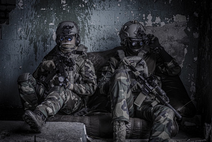 Two airsoft players sitting against a wall