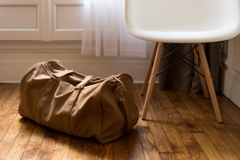 A green holdall on the floor next to a chair
