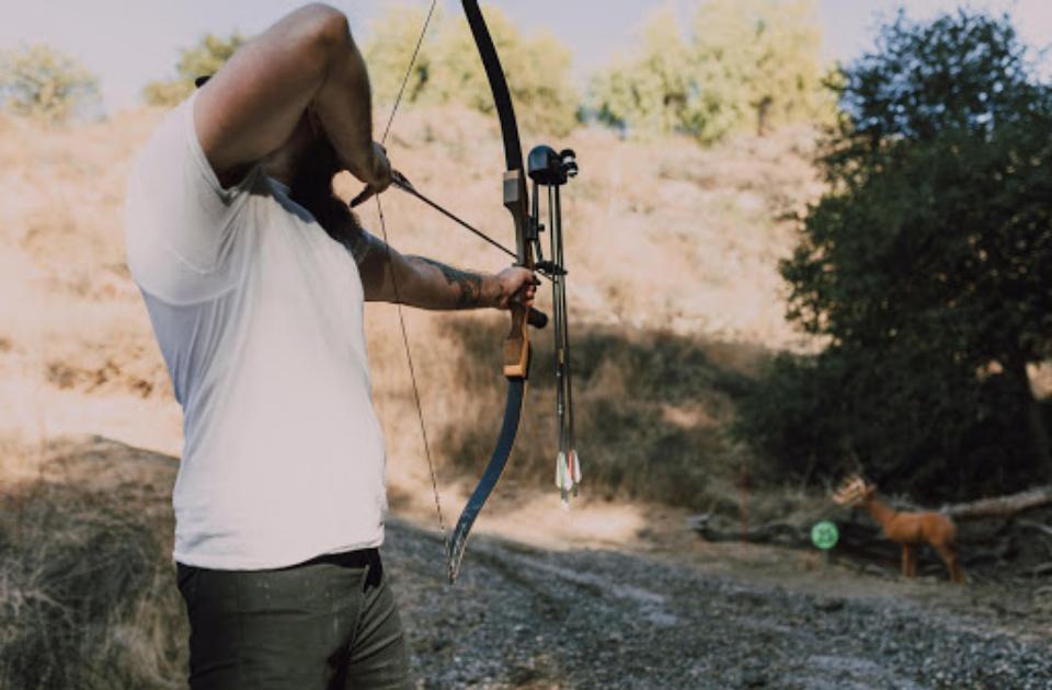 A man drawing a bow, aiming at fake game