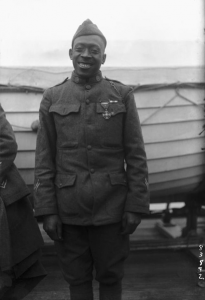 """Pvt. Henry """"Black Death"""" Johnson posing for a photo in front of a boat"""