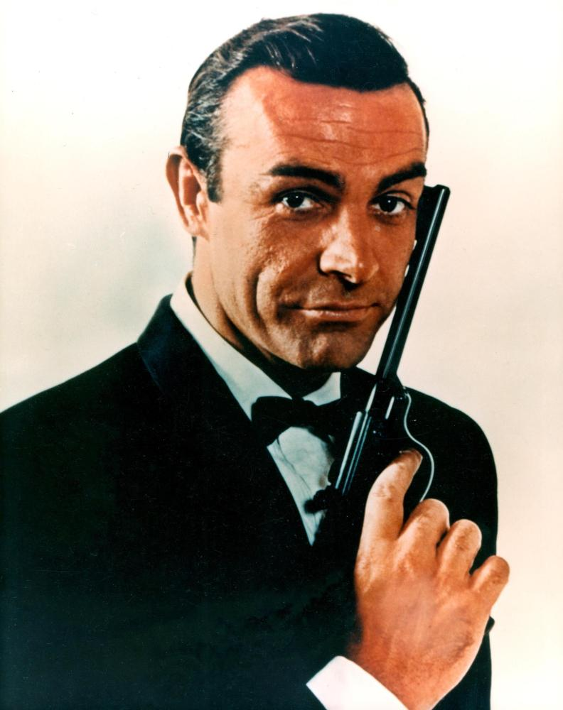 Sean Connery as James Bond, posing with an air pistol.
