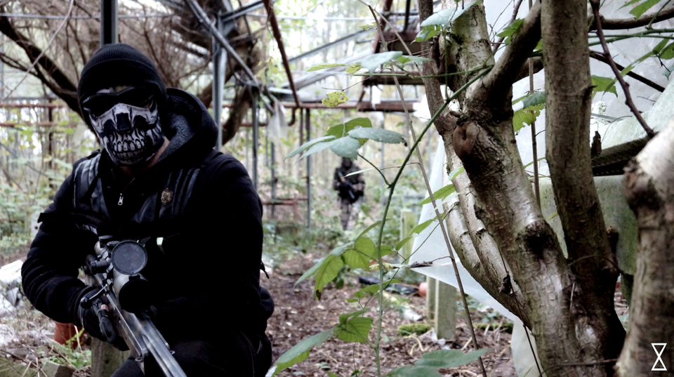 Man posing with airsoft sniper in a forest.