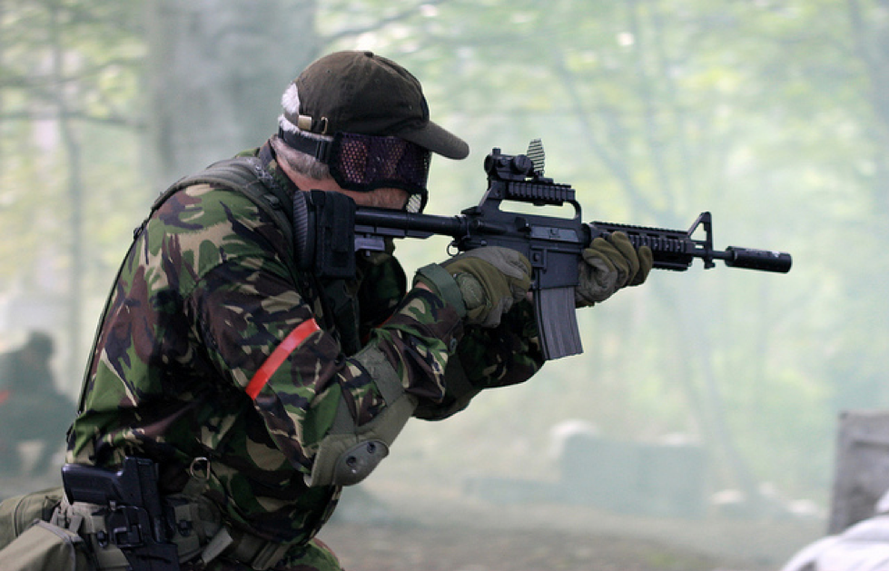 Man aiming whilst equipped with two Airsoft guns