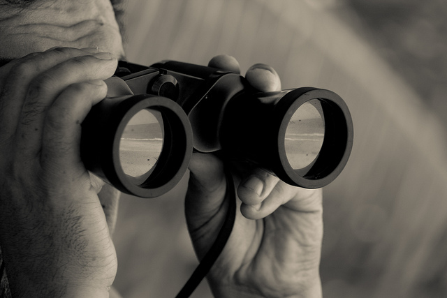 A spy looks through binoculars.