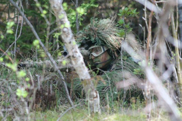 Airsoft sniper blending into shrubbery