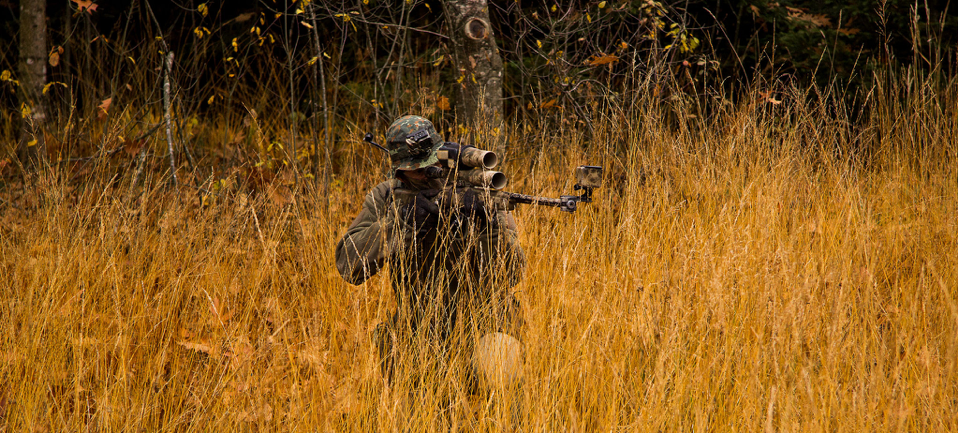 Sniper in the grass who is equipped with airsoft guns.