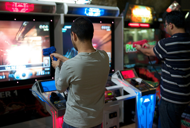 Two men using a Time Crisis arcade machine.