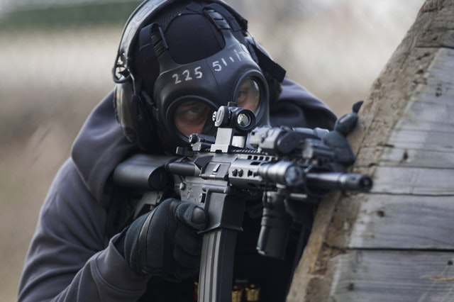 Man aiming airsoft rifle from behind cover