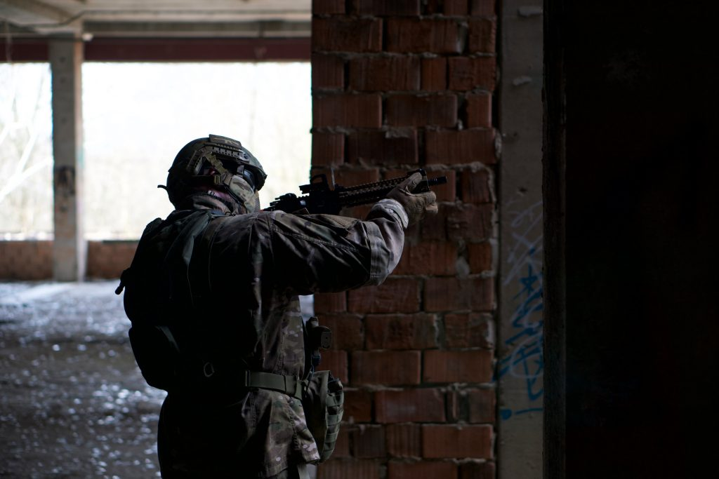 Person playing airsoft wearing camouflage, helmet and full mask