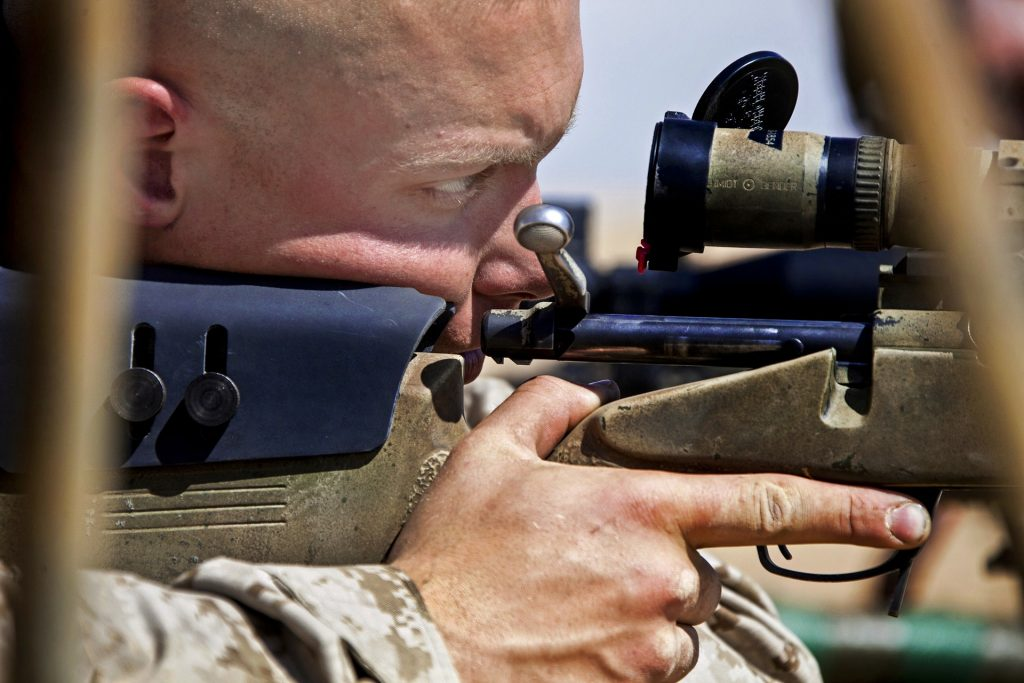 A man looking down a telescopic scope on a sniper rifle