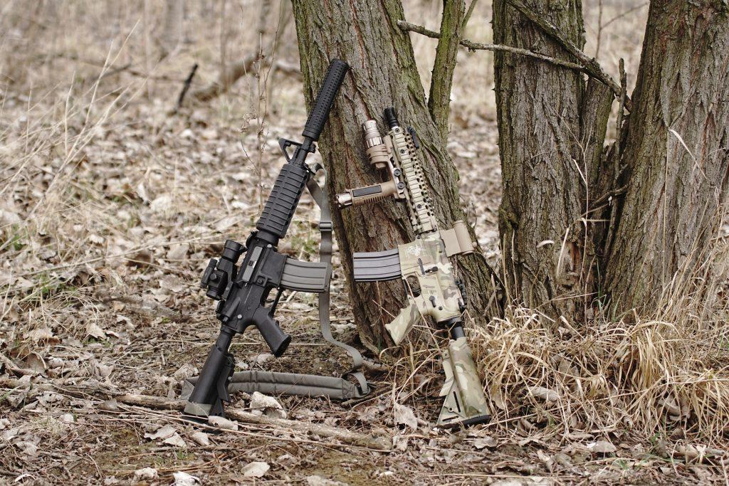 Two Airsoft Guns balanced against tree