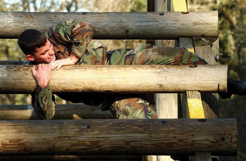 Army recruit climbing a wooden ladder