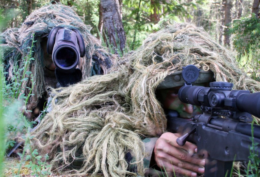 US Army sniper with a spotter wearing camouflage