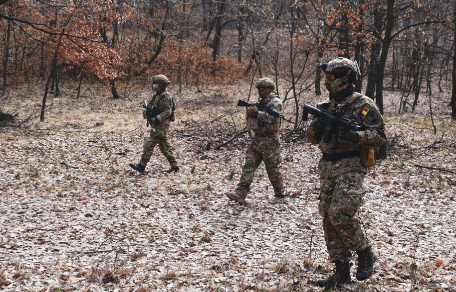 Three soldiers walking through woodland