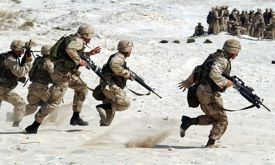 Men running in military gear with guns