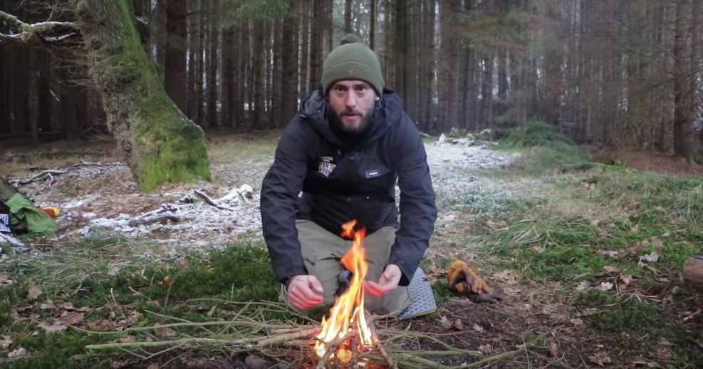 Man kneeling down by a fire