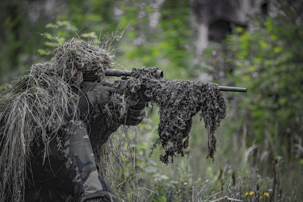 Person holding sniper rifle wearing a ghillie suit