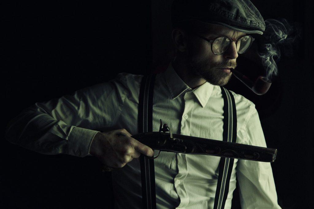 Man wearing cap holding shotgun